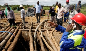 Rescuers gather around a mine shaft at the scene in Kadoma