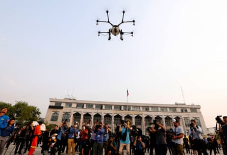 An officer from the Bangkok Metropolitan Administration uses agricultural drones to spray a water based solution in the air during the operation in an attempt to ease the effects of heavy smog