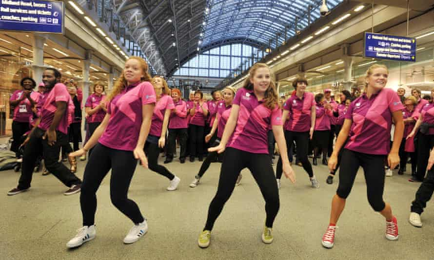 Olympic volunteers dance during a flash-mob at the Eurostar terminal in St Pancras station, London