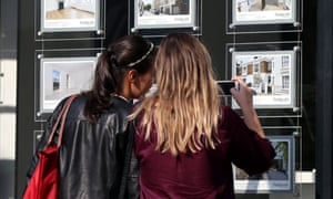 Young women look at an estate agent window