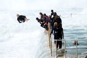 A teenage boy jumps off the edge of the South Curl Curl ocean pool into an incoming wave.