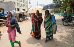 Women walk through Old Gugaon.