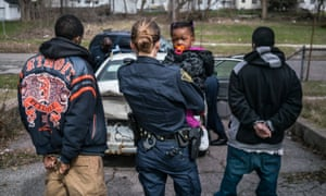 An officer holds a small child while her father is being searched and questioned.