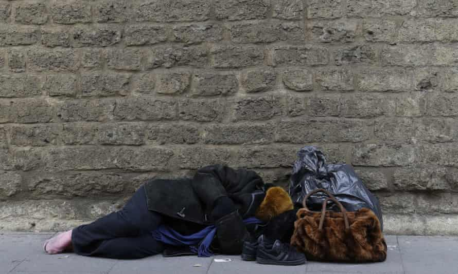 A homeless person sleeps near the Vatican walls in downtown Rome