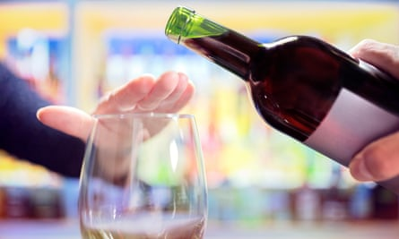 Woman's hand rejecting more alcohol from wine bottle