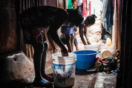 Linet (L), 16, who is about 3 months pregnant, helps to wash clothes.