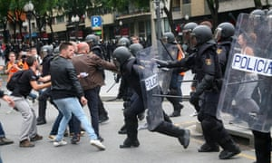 Spanish riot police clash with people outside a polling centre in Tarragona on the day of the referendum
