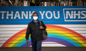 A commuter walks past a message to the NHS at Cannon Street station in London