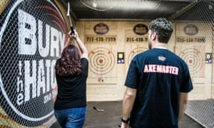 A customer throws an axe under the watchful eye of an axe-master at Bury the Hatchet in Brooklyn, New York.