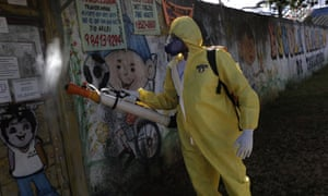 A government employee disinfects a public school as a measure against the spread of the new coronavirus, in the Taguatinga neighbourhood of Brasilia, Brazil, Tuesday, 28 July 2020.
