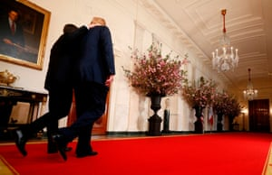 Donald Trump and Emmanuel Macron walk through the cross hall of the White House as they depart following their joint news conference in Washington