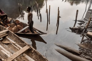 A man and woman in a canoe floating on an oily river in Bayelsa, Nigeria, 8 June 2018