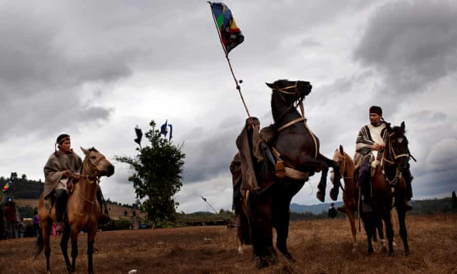 A Mapuche Indian sits on his horse as he waves the green, red and blue indigenous flag colors during a 'Guillatun', a spiritual ceremony to ask for the well-being of the clan and strengthen ties, in Ercilla, Chile.