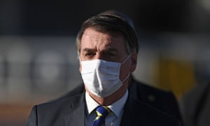 Brazilian President Jair Bolsonaro wears a face mask as he arrives at the flag-raising ceremony before a ministerial meeting at the Alvorada Palace in Brasilia, Brazil, in May 2020.
