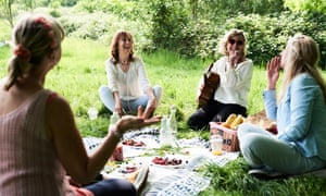 Group of women at a picnic in park, as lockdown in England is eased.