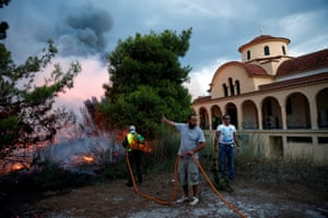 People try to extinguish a wildfire burning next to a church in Rafina