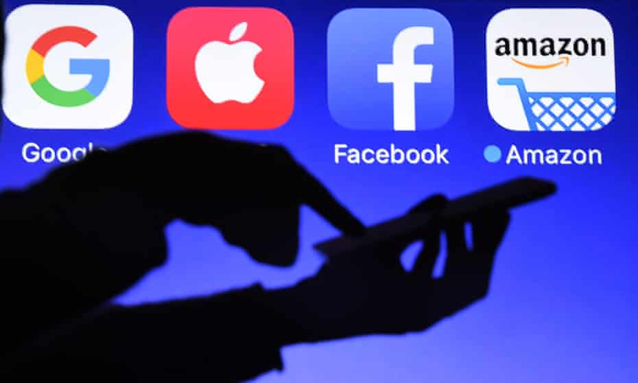 A smartphone being operated in front of the logos of Google, Apple, Facebook and Amazon