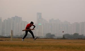 A boy plays cricket amid smog at a playground in Noida on the outskirts of Delhi, India, on 14 November.