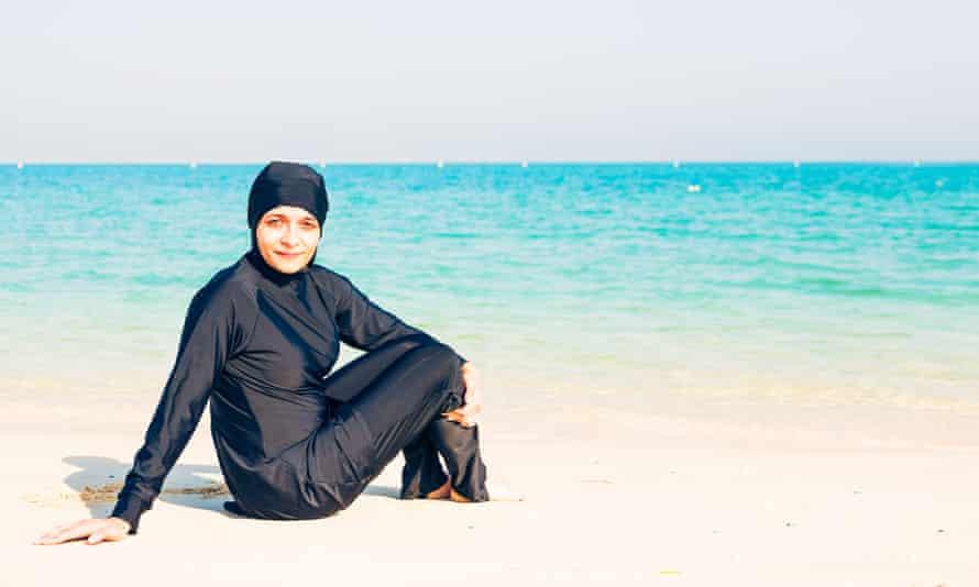 A woman wearing a burkini on the beach.