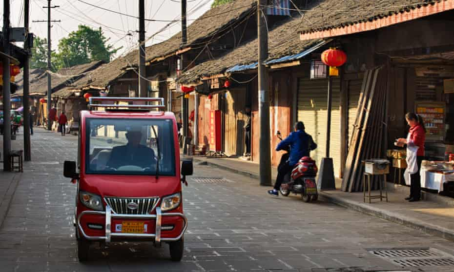 One-person car drives through the streets, passing shops, in Pengzhen, China.