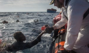 Crew members from the Moas Phoenix vessel help survivors into a rescue boat