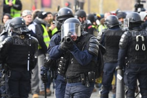 A riot police officer aims a rubber bullet at the line of protesters