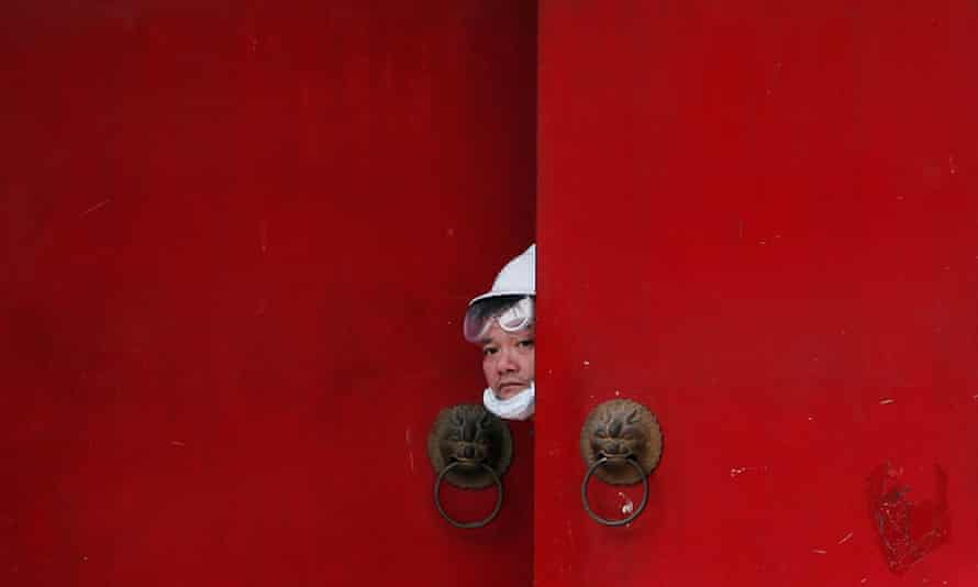 A man in a white hard hat peeps out from a doorway during a protest in Hong Kong's New Territories on Saturday.
