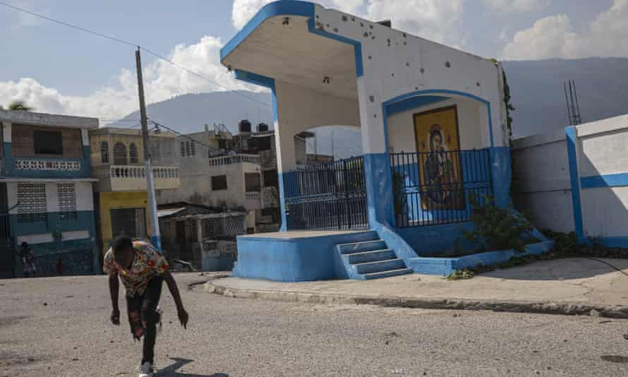 A man runs for cover as he crosses a barricaded street in the gang-controlled Bel Air neighborhood of Port-au-Prince.