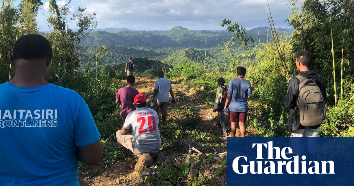 Fijian doctors trek up and down mountains to reach remote village with Covid vaccines – video
