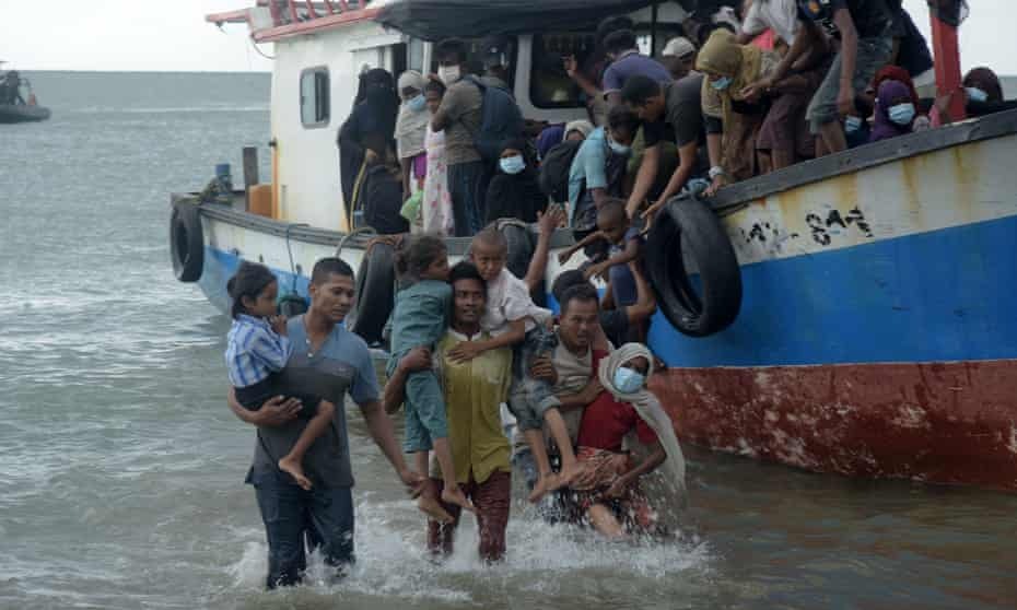 Locals rescue Rohingya refugees from a ship on Lancok beach, Indonesia