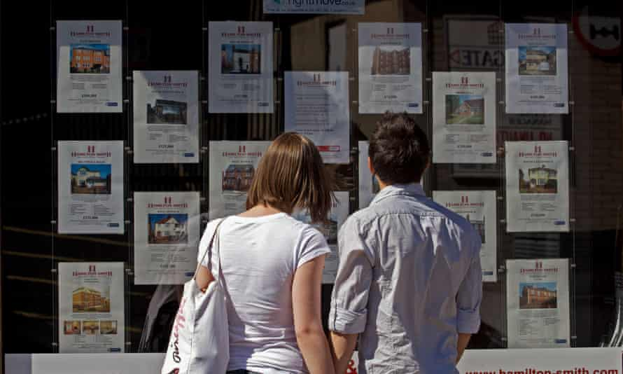 a couple look at houses for sale in a real estate agent's window