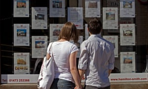 First-time buyers peruse homes for sale in an estate agents window.
