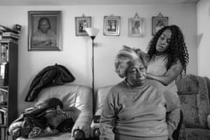 Hermine Grocia has her hair plaited by Krystyna, her granddaughters, from Windrush generation portraits by Jim Grover