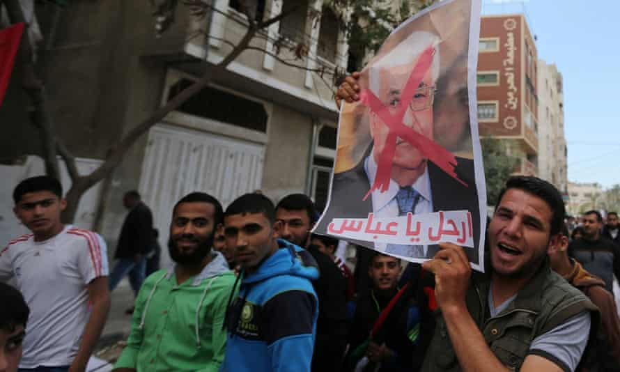 Hamas supporter holds a poster of President Abbas during a protest in southern Gaza.