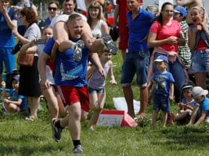 Krasnoyarsk, RussiaA man carries his wife while racing in the Wife Carrying competititon