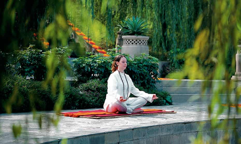 A woman in white clothes meditating on a mat at a retreat in the Himalayas.