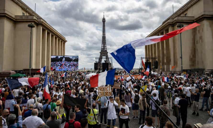 A large group of protesters, some waving French flags, between two buildings with the Eiffel Tower central in the background