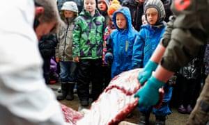 Children watch as Marius, a male giraffe, is dissected, at the Copenhagen zoo, in Denmark
