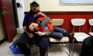 Neldis Diaz Masariegos, 25, and his son Nelvis Emmanuel Diaz Hererra, 7, of Guatemala wait inside the Sacred Heart Catholic Church Center on 24 March 2016 in McAllen, Texas.