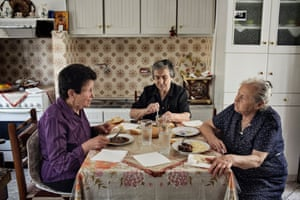 Mpalli is photographed (left) at lunch with Aimilia Kamvisi (centre) and Maristsa Mavrapidou in Kamvisi's home in Skala Sykamineas.
