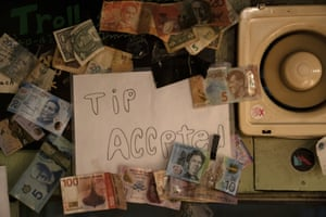 Banknotes from around the world are pinned to the wall of a bar