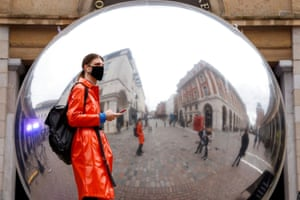 A person wearing a face mask is reflected in an artwork entitled A=V by Ben Cullen Williams in London, UK