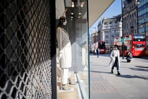 A pedestrian wearing a face covering walks past a clothes shop, closed down due to Covid-19 restrictions, in central London