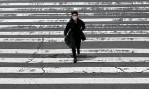 OSAKA, JAPAN - MAY 28: A pedestrian wears a protective mask while crossing the street in the Umeda shopping and entertainment district on May 28, 2021 in Osaka, Japan.  The government is expected to announce an extension of the current state of emergency later today as Japan continues to grapple with a fourth wave of coronavirus that has seen hospital beds in Osaka reach 96 percent of capacity and requests for various organizations to cancel the next Olympics.  (Photo by Buddhika Weerasinghe / Getty Images)