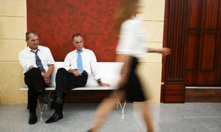 Two businessmen looking at a passing woman's legs