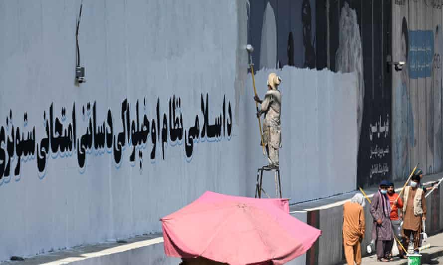 A man paints over murals on a concrete wall in Kabul with a message reading 'For an Islamic system and independence, you have to go through tests and stay patient'.