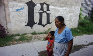 A grandmother and grandson walk by the Barrio18's insignia in the Ilopango district of San Salvador, El Salvador.