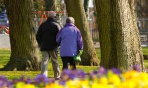 A middle-age couple walking through a park.