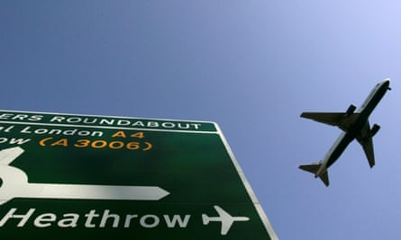 A plane flies over a road sign directing motorists to Heathrow