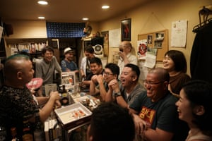 Patrons laugh as they listen to the entertainer Tadashi Yokoda, far left, in a bar